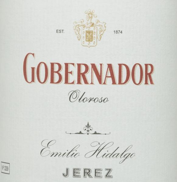 Der Gobernador Oloroso von Emilio Hidalgo ist ein über viele Jahre gereifter, rebsortenreiner Sherry aus der spanischen Weinregion D.O. Jerez. Im Glas leuchtet eine strahlende Mahagoni-Farbe. Dieser noble Sherry überzeugt die Nase als auch den Gaumen mit seinen kräftigen nussigen Aromen - es präsentieren sich Wallnüsse, Haselnüsse und Mandeln. Am Gaumen überzeugt dieser spanische Wein mit seinem vollmundigen und trockenen Charakter und einen lang anhaltenden Nachhall. Vinifikation des HidalgoGobernador Oloroso Die von Hand gelesenen Trauben werden entrappt, sanft gepresst und der daraus entstandene Most temperaturkontrolliert im Edelstahltank vergoren. Im Anschluss wird der junge Wein abgezogen, aufgespritet und zur ersten Reife in Fässer aus amerikanischer Eiche gelegt. Dabei werden die Fässer nur zu einem gewissen Teil (maximal 85%) gefüllt, sodass sich die charakteristische Flor (eine Hefeschicht) entwickeln kann, die den Wein luftdicht abschließt und ihm das sherry-spezifische Aroma verleiht. Nach erfolgter Reife wird der Wein ins traditionelle Solera-System geleitet, in welchem typgleiche Sherrys in übereinander gereihten Fässern ausgebaut werden. In den unteren Fässern (Solera) lagern hierbei die ältesten Weine, während in den oberen Reihen (Criaderas) die jüngsten Weine aufliegen. Der für den Verkauf bestimmte Sherry wird immer den unteren Fässern entnommen. Hierbei wird jedoch lediglich ein kleiner Teil (maximal ein Drittel) entnommen und der entnommene Teil sodann durch Sherry aus den oberen Reihen aufgefüllt. Das ganze Prinzip wird bis in die obersten Fässer fortgeführt, wo dem Sherry junger Wein, der Mosto, zugesetzt wird. Im Solera verliert der Amontillado an Flor und der oxidative Reifeprozess setzt ein. Während dieser Phase entwickelt er seine aromatische Fülle und die kräftige Farbe. Speiseempfehlung für denGobernador Oloroso Emilio Hidalgo Dieser trockene Sherry aus Spanien passt eignet sich am besten leicht gekühlt als Aperitif. Aber auch würzigen,r